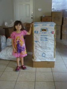 A proud Zoe poses next to the R2D2 they created while her sister is inside the robot.